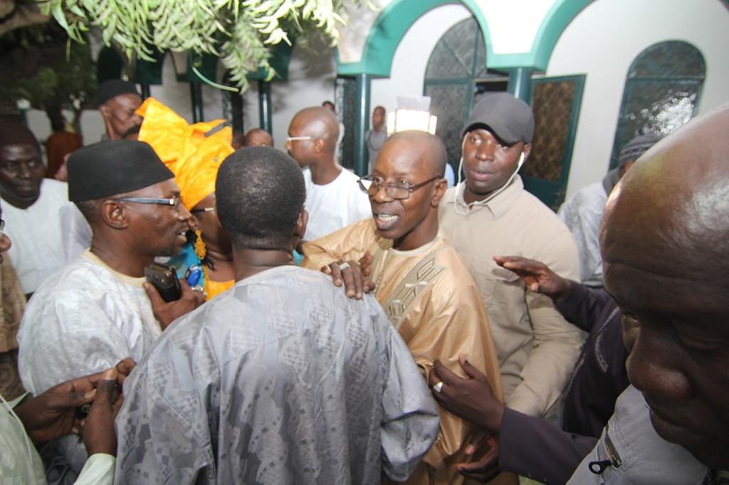Mamadou Oumar Bocoum  en tenue traditionnelle marron et montures tenant l'épaule d'un ami qui le félicitait