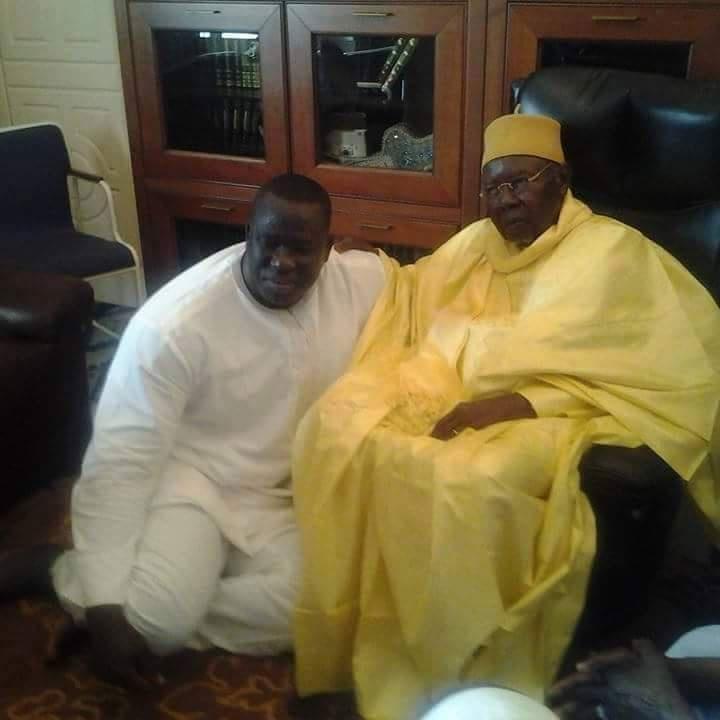 """Le lutteur Yekini, en vrai """"talibe"""" Tidiane, assis aux pieds de son marabout Serigne Abdoul Aziz Sy"""